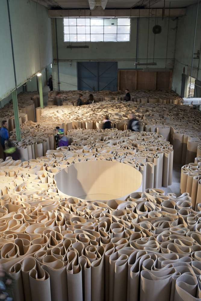 2100 meters of corrugated cardboard are massed in folds that stand approx seven feet to create a huge labyrinth of paper.